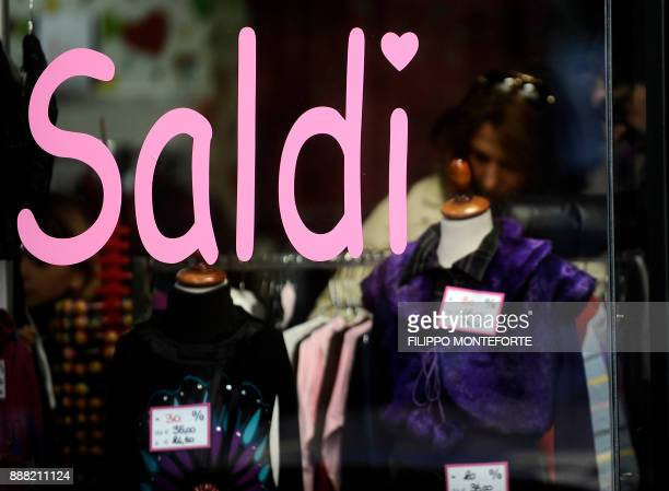 A couple is seen through a shopwindow near Via Condotti one of central Rome's main shopping streets for the second day of sales on January 3 2010...
