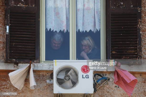 A couple is seen through their home window during lockdown on March 23 2020 in Rome Italy As Italy extends its nationwide lockdown to control the...