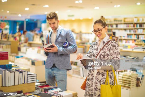 couple is selecting new books in the bookstore - book shop stock pictures, royalty-free photos & images