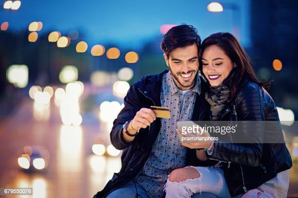 Couple is shopping online on the bridge in the night
