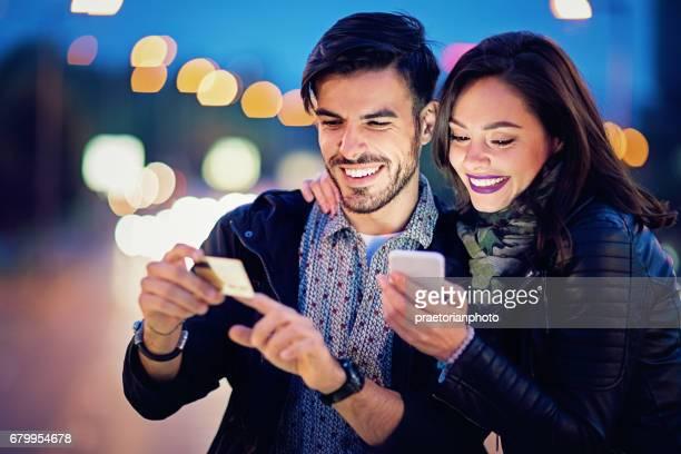 Couple est le shopping en ligne sur le pont dans la nuit