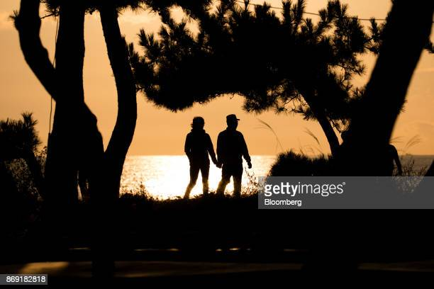 A couple is silhouetted as they walk through Gyeongpo beach near the Gangneung Ice Arena one of the venues for the 2018 PyeongChang Winter Olympic...