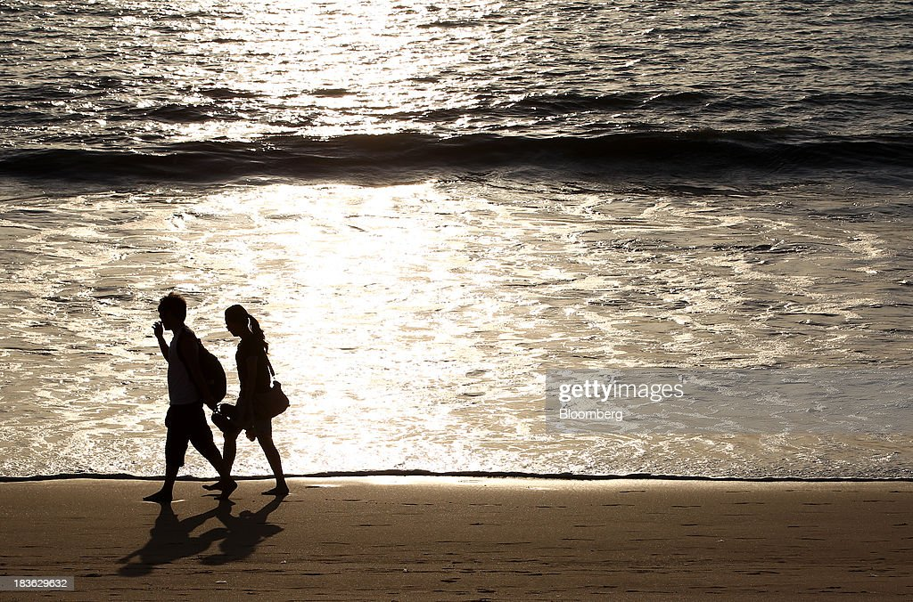 A couple is silhouetted while walking along a beach in Jimbaran, Bali, Indonesia, on Saturday, Oct. 5, 2013. Indonesia's central bank kept its key interest rate unchanged after its most aggressive tightening cycle in almost eight years as inflation pressure eased. Photographer: SeongJoon Cho/Bloomberg via Getty Images