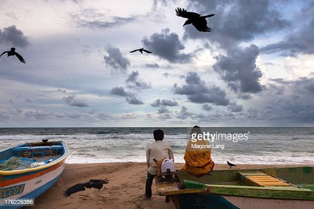 CONTENT] A couple is sitting on a boat and watching the ocean by a cloudy late afternoon with crows in the sky in Mahabalipuram Tamil Nadu India