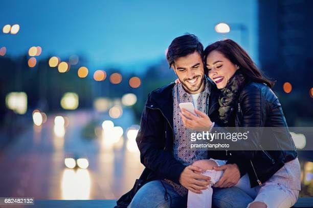 Couple is texting on the bridge in the night