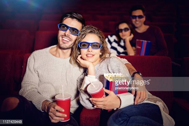 couple is watching 3d movie in the cinema theater - girlfriends films stock pictures, royalty-free photos & images