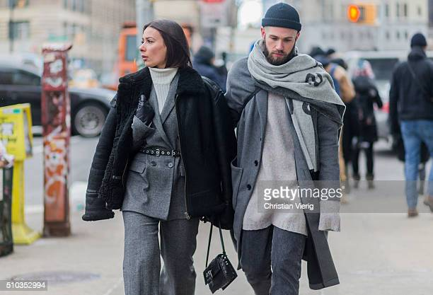 A couple is wearing a grey suit and wool jacket and a black leather jacket seen outside Lacoste during New York Fashion Week Women's Fall/Winter 2016...