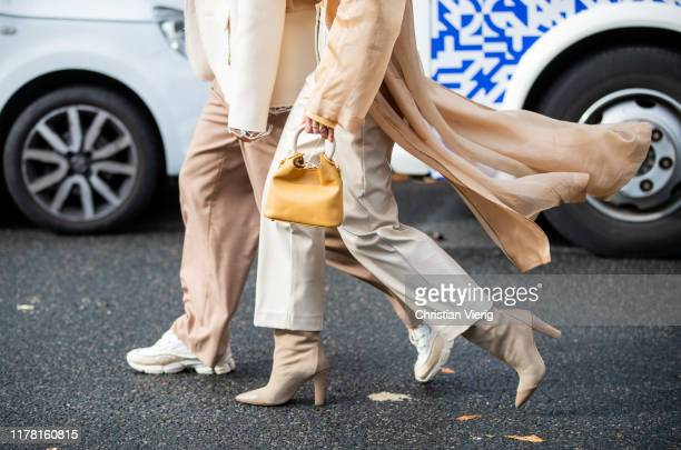 Couple Jean-Sebastien Roques and Alice Barbier seen wearing ankle boots, mustard mini bag, long silk top outside Akris during Paris Fashion Week...