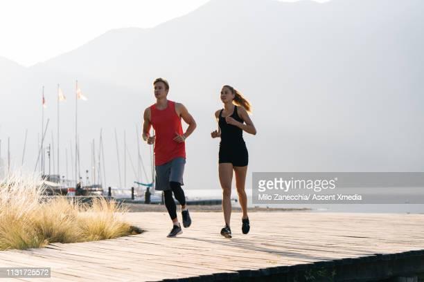 couple jog along lake promenade in the sun - uferpromenade stock-fotos und bilder