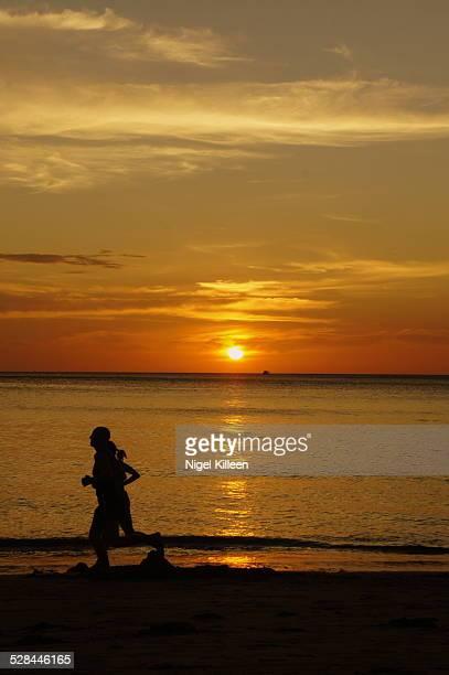 A couple jog on the beach at sunset Koh Lanta Thailand