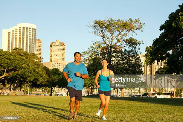 couple jogging at beach park - adulto di mezza età foto e immagini stock