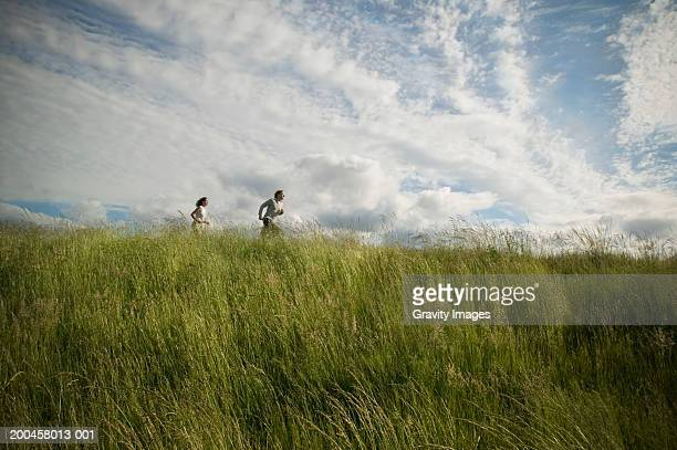 couple jogging in countryside, low angle view (wide angle) - gras stock pictures, royalty-free photos & images