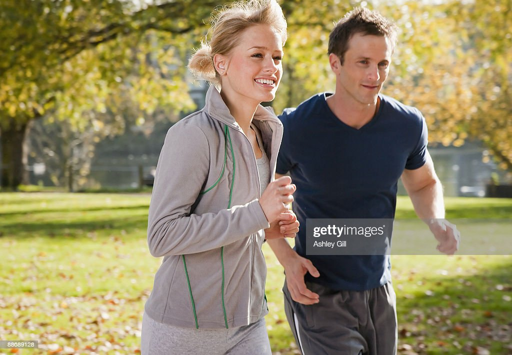 Couple jogging in park in autumn : Stock-Foto