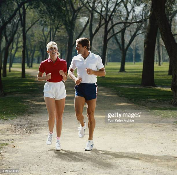 Couple jogging in park, smiling