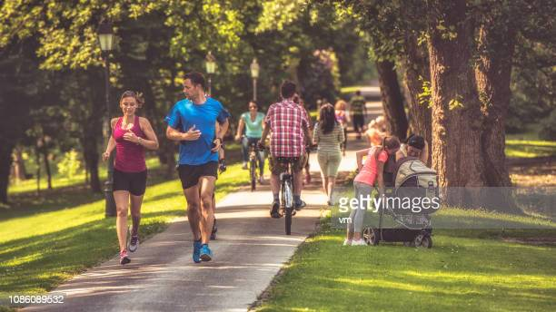 couple jogging in the park - jogging stock pictures, royalty-free photos & images