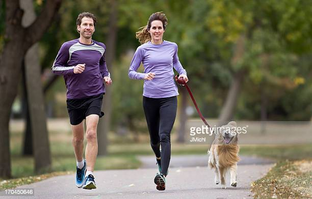 A couple jogging in the park with their golden retriever