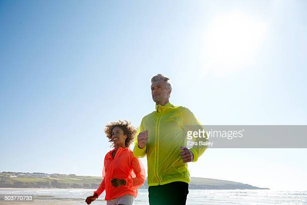 Couple jogging on a deserted beach.