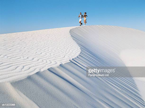 Couple Jogging on a Sand Dune