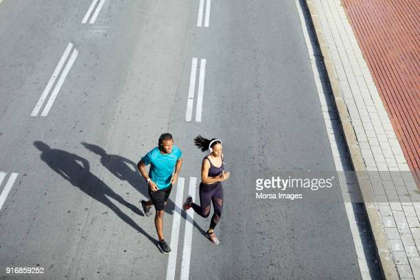 """couple jogging on city street during sunny day""""n - forward athlete stock pictures, royalty-free photos & images"""