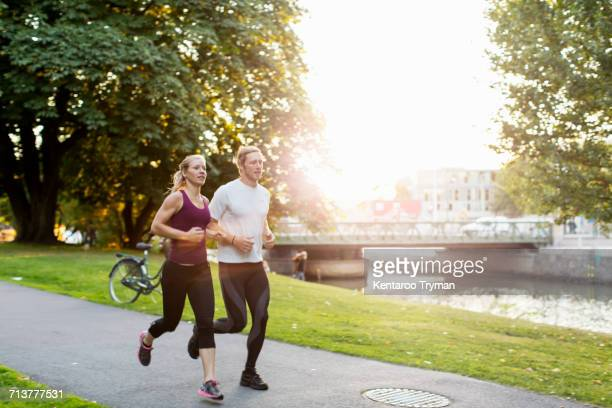 Couple jogging on footpath at park during sunrise