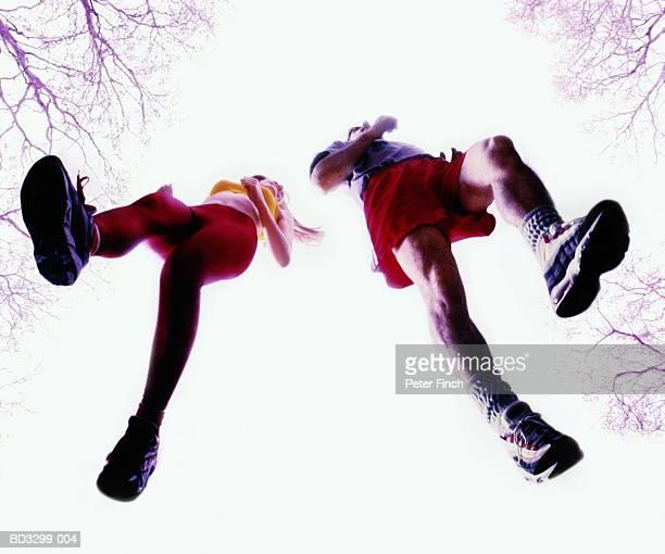 Couple jogging outdoors, upward view (Digital Composite)
