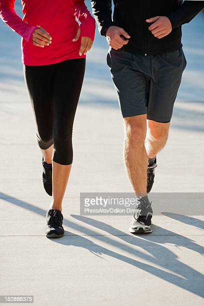 Couple jogging side by side, low section