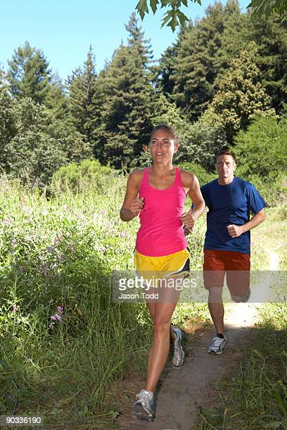 couple jogging through meadow in forest - jason todd stock photos and pictures