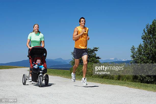 Couple jogging while pushing a baby stroller