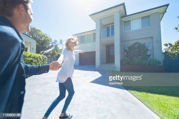 couple joyfully running into their new home. - moving house stock pictures, royalty-free photos & images