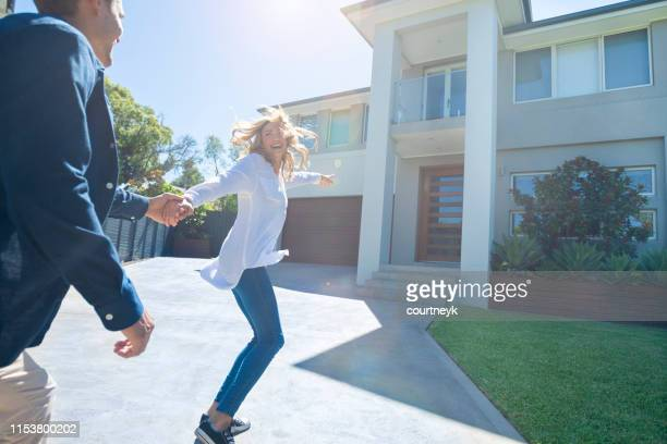couple joyfully running into their new home. - young couple stock pictures, royalty-free photos & images