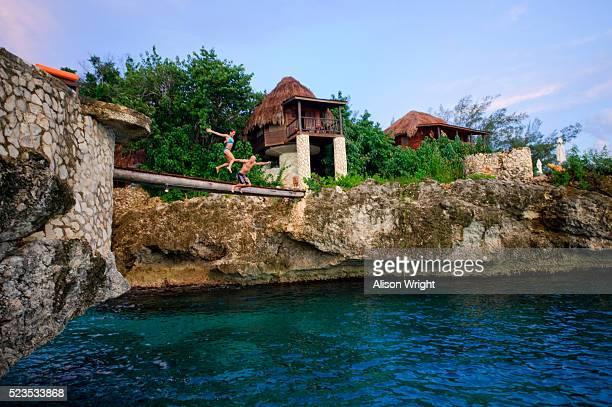 Couple jumping from bridge, Montego Bay, Jamaica
