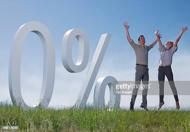 Couple jumping in field next to percent symbol