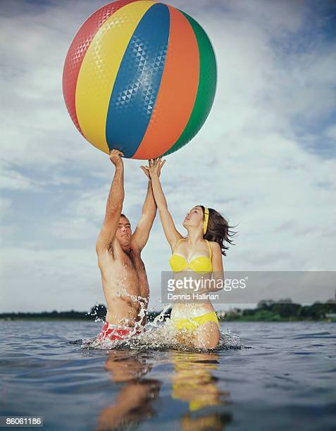 couple jumping in water reaching for large beach ball - man with big balls stock photos and pictures