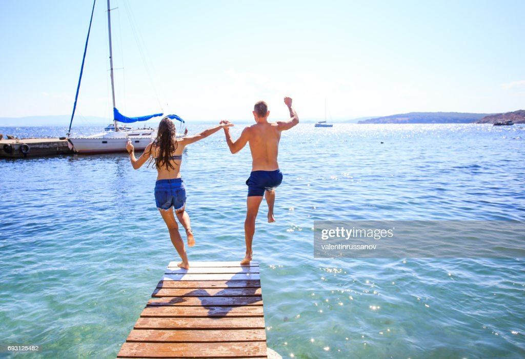 Couple jumping into water : Stock Photo