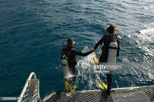 Couple jumping off back of boat wearing scuba diving equipment
