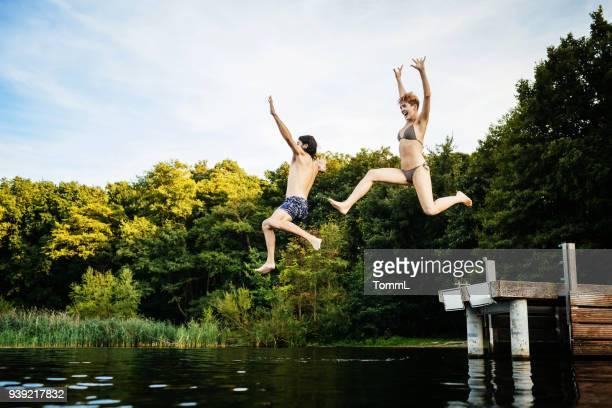 paar von jetty zusammen an einem see zu springen - see stock-fotos und bilder