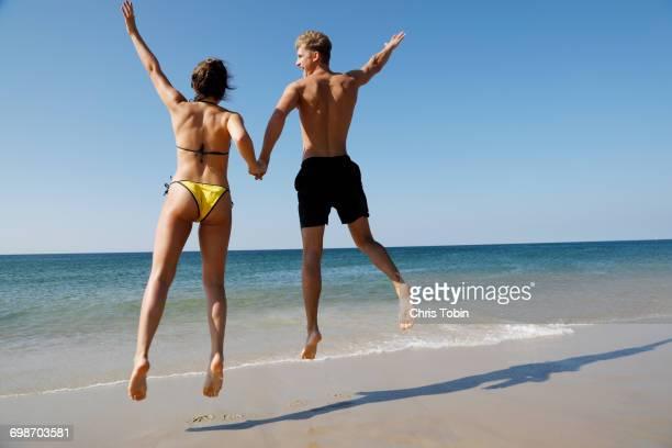 Couple jumping on beach near water