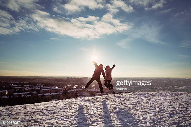 Couple jumping on snow covered mountains against sky