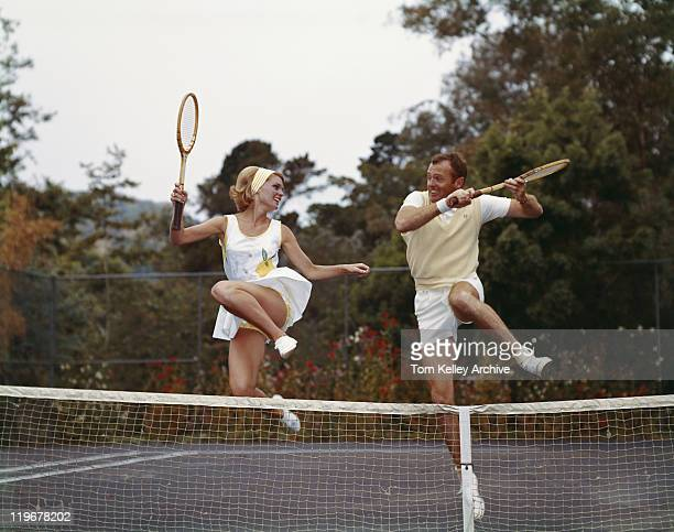 Couple jumping on tennis court, smiling