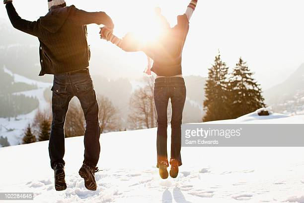 Couple jumping outdoors in snow