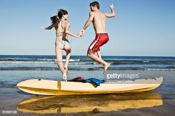 Couple Jumping Over a Sea Kayak