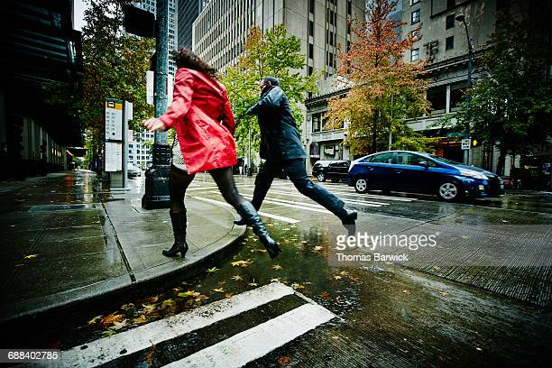 Couple jumping over puddle on city street