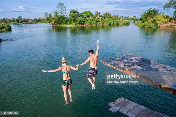 A couple jumps into the water, holding hands.