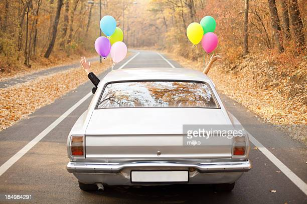 a couple just married with balloons tied to their car - newlywed stock pictures, royalty-free photos & images