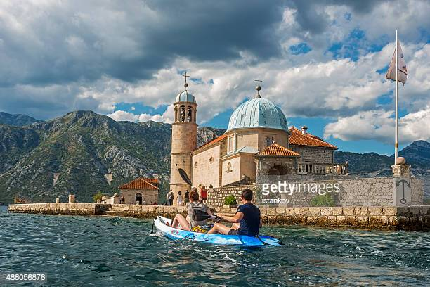 couple kayaking in front of our lady of the rocks - kotor bay stock pictures, royalty-free photos & images