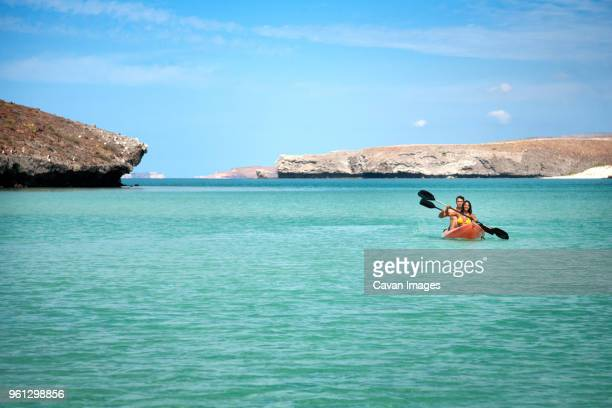 couple kayaking in sea against sky - cabo san lucas stock pictures, royalty-free photos & images