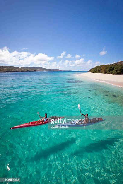 Couple kayaking in tropical setting