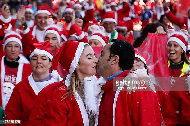 Couple kiss across the finish line after the circuit of popular 5.5k Santa Claus race in Madrid. Six thousand runners dressed in Santa Claus costume...