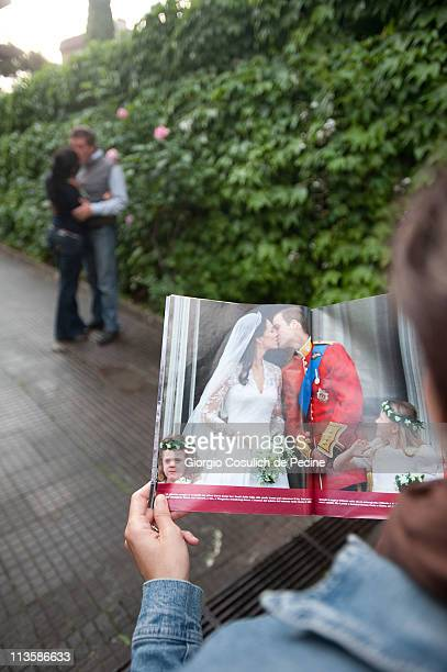 A couple kiss as a girl reads an Italian magazine showing photographs of Prince William Duke of Cambridge and Catherine Duchess of Cambridge...