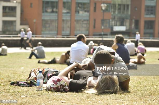 A couple kiss as people relax and enjoy the hot weather in Castle Park Bristol